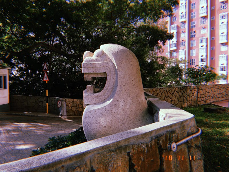 Cute smiling stone lion sculpture by Rodolfo Nolli at HKU's High West